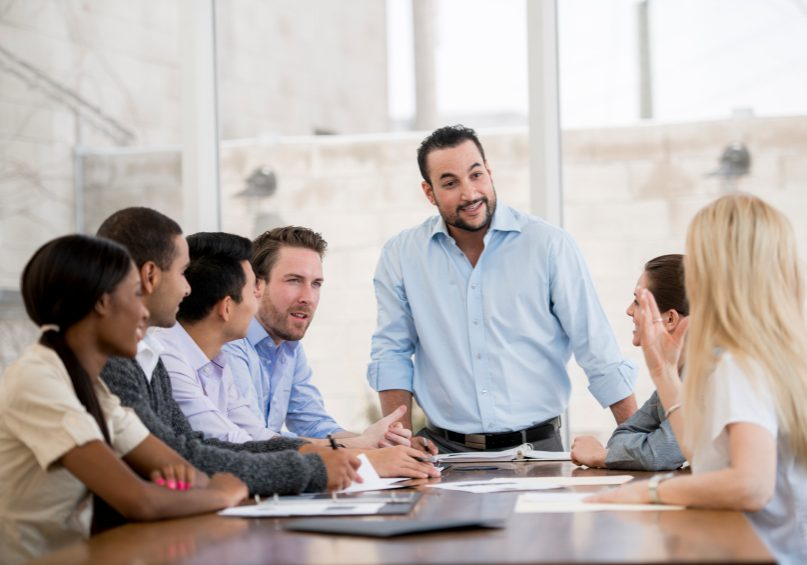 A multi-ethnic group of business associates having a discussion at work during a meeting in a room with natural light.