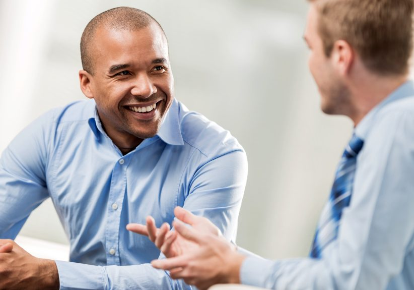 Two businessmen sitting in the office and communicating. Focus is on happy African American businessman.